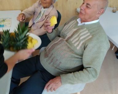 Dwoje uśmiechniętych seniorów. Siedzą przy stole. Częstują się ananasem.
