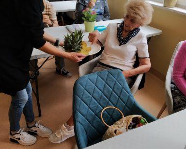 Seniorzy przy stołach. Kierowniczka Ilona Gajewska częstuje seniorów ananasem.