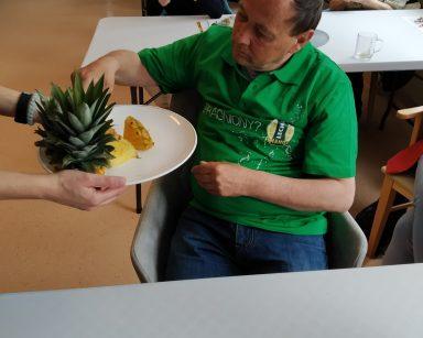 Seniorzy przy stołach. Senior częstuje się ananasem. Seniorzy siedzący za nim, już jedzą plastry owocu.