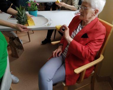Seniorzy przy stołach. Seniorka częstuje się ananasem. Seniorzy siedzący za nią, już jedzą plastry owocu.