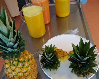 Metalowy wózek. Na nim ananas, talerz z zielonym pióropuszem ananasa i pokrojonym owocem. Obok dzbanki z sokami.