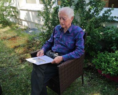 Ogród. W cieniu siedzi senior. Na kolanach trzyma ulotkę z zestawem ćwiczeń.