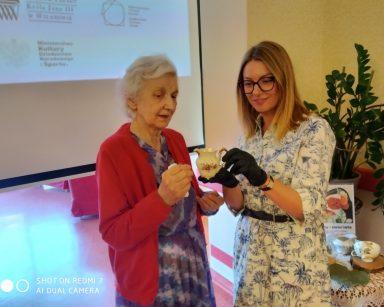 Przy ekranie projektora seniorka i psycholożka Maria Skubich-Wiczling. Oglądają dzbanuszek z wzorem w kwiaty.