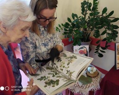 Koło stolika seniorka i psycholożka Maria Skubich-Wiczling. Oglądają książkę z obrazkami różnych roślin.