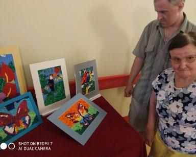 Dwoje seniorów przy stoliku. Na blacie kolorowe obrazki zwierząt i roślin. Obrazki są wykonane z kulek z bibuły.