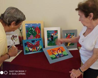 Dwie seniorki przy stoliku. Na blacie kolorowe obrazki zwierząt i roślin. Obrazki są wykonane z kulek z bibuły.