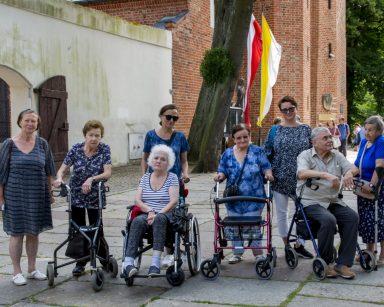 Mieszkańcy, wolontariusze i pracownicy podczas spaceru. Plac przed budynkiem z czerwonej cegły.