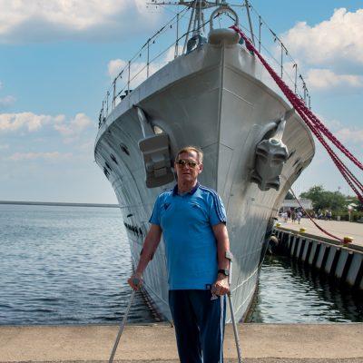 Słoneczny dzień błękitne niebo. Senior stoi na nabrzeżu. Za nim, na morzu przycumowany statek.