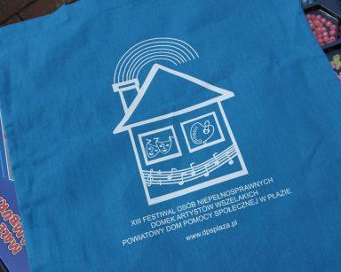 Niebieska torba z białym napisem XIII Festiwalu Osób Niepełnosprawnych Domek Artystów Wszelakich Powiatowy DPS w Płazie.