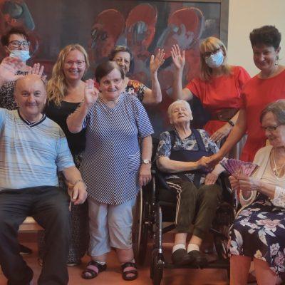 Agnieszka Sut, wolontariuszka, dyrektorka Agnieszka Cysewska, pracownicy i seniorzy pozują do zdjęcia. Uśmiechają się i machają.