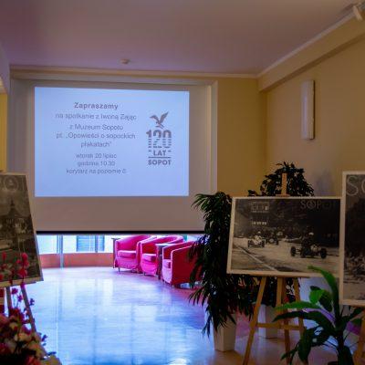 Przy ścianach czarno-białe plakaty z napisem Sopot. Na środku ekran projektora. Na nim zaproszenie na spotkanie z Iwoną Zając.