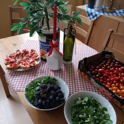 Na stole obrus w biało-czerwona kratkę. Butelka oliwy, kartonik z pomidorkami, talerze z winogronami, roszponką i kanapkami.