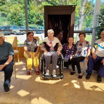 Ogród zimowy. Seniorzy i fizjoterapeutka Martyna Józefczyk w rzędzie. Uśmiechają się do zdjęcia. Za nimi tężnia solankowa.