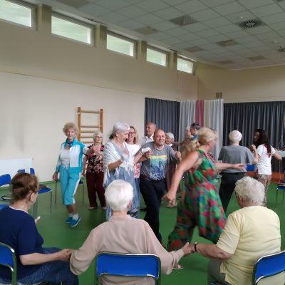 Jasna sala. Agnieszka Sut, wolontariuszki i seniorzy. Biorą udział w zajęciach Biodanzy. Tańczą, trzymają się za ręce.