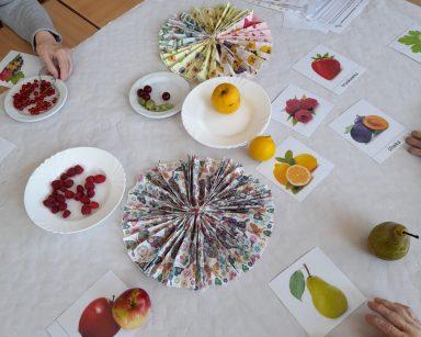 Widok z góry. Na stole obrazki i nazwy owoców, kolorowe serwetki. Na talerzach świeże owoce: maliny, porzeczki, agrest i inne.