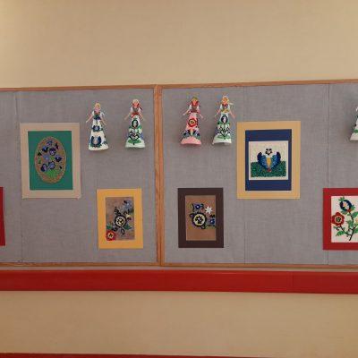 Tablica na ścianie. Na niej wystawa prac z kaszubskimi wzorami. Obrazki i laleczki wyklejane kulkami z kolorowej bibuły.