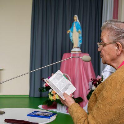 Jasna sala. Pani Otylia czyta różaniec. W tle figurka Matki Boskiej.