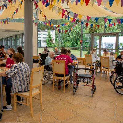 Ogród zimowy udekorowany kolorowymi chorągiewkami. Przy stolikach seniorzy, wolontariusze i pracownicy grają w gry planszowe.