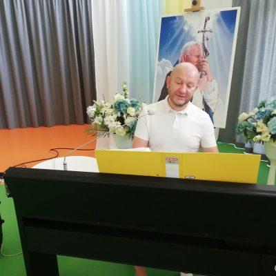 Kierownik Arkadiusz Wanat gra na pianinie. W tle portret papieża Jana Pawła II i dekoracje z kwiatów.