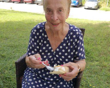 W zacienionym ogrodzie, na rattanowym fotelu siedzi seniorka. Uśmiecha się. W rękach trzyma wafelek z lodem i łyżeczkę.