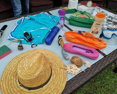 Rattanowy stół. Na blacie różne przedmioty kojarzące się z wakacjami. Wśród nich słomkowy kapelusz, kąpielówki, muszle.