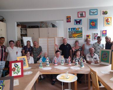 Dyrektorka Agnieszka Cysewska, mieszkańcy i pracownicy. Przed nimi na stołach obrazki i lalki z kolorowymi kaszubskimi wzorami.