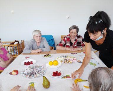 Jasna sala. Przy stole terapeutka Ania Rzepczyńska i seniorki. Na blacie świeże owoce, ich obrazki, kolorowe serwetki.