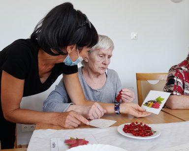 Przy stole terapeutka Ania Rzepczyńska. Pokazuje seniorce obrazek z porzeczkami. Przed nimi na blacie świeże porzeczki i maliny.
