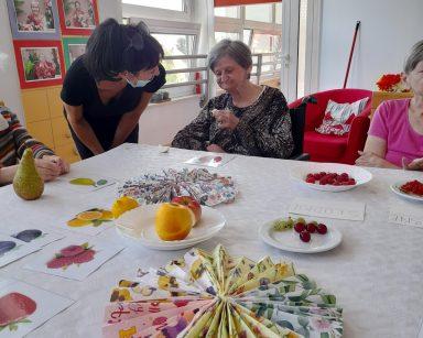 Terapeutka Ania Rzepczyńska i seniorki przy stole. Na blacie owoce, obrazki, kolorowe serwetki. Jedna z seniorek smakuje jabłko.