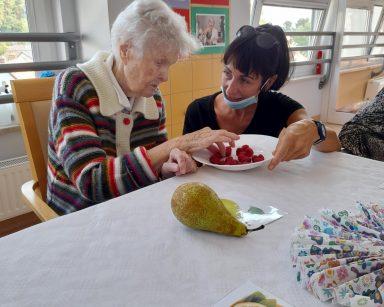 Przy stole terapeutka Ania Rzepczyńska częstuje seniorkę malinami. Na blacie owoce, obrazki, kolorowe serwetki.