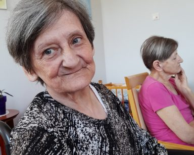 Jasna sala. Na pierwszym planie uśmiechnięta seniorka. W tle inna seniorka siedzi na krześle.