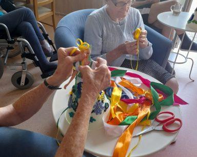 Na sali przy stolikach seniorzy. Na blatach papierowe lalki, kolorowe wstążki. Seniorki wiążą kokardki.