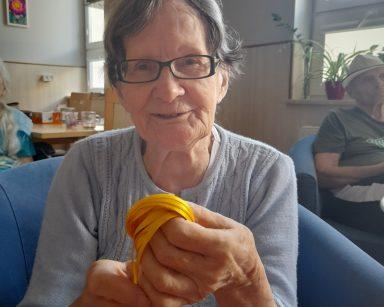 Seniorka siedzi na fotelu. Uśmiecha się. W dłoniach trzyma żółtą wstążkę. W tle inni seniorzy na sali.