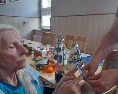 Seniorka wspólnie z terapeutką wiąże wstążkę. Z tyłu na blacie papierowe lalki i kolorowe wstążki.