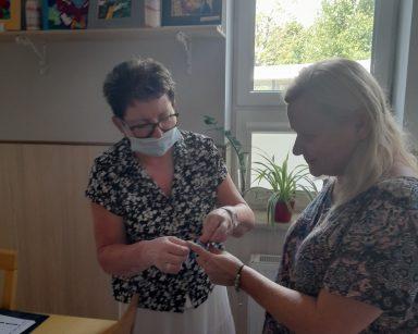 Kierowniczka Mariola Ludwicka i neurologopedka Anna Szmaja-Wysocka zawiązują wspólnie niebieską wstążkę.