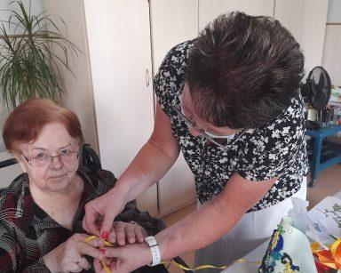 Seniorka siedzi przy stole. Nad nią pochyla się kierowniczka Mariola Ludwicka. Wspólnie wiążą kokardkę z żółtej wstążki.
