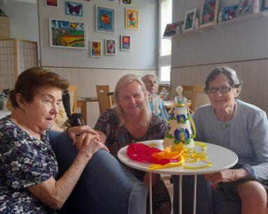 Na sali roześmiane seniorki i neurologopedka Anna Szmaja-Wysocka. Na stoliku kolorowe wstążki i papierowa lalka.