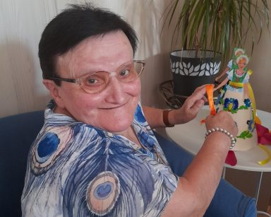 Seniorka uśmiecha się. W dłoniach trzyma pomarańczową kokardkę. Za nią, na blacie papierowe lalki w kaszubskich strojach.
