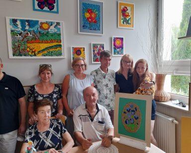 Dyrektorka Agnieszka Cysewska, seniorzy, pracownicy. Na blacie wystawa inspirowana wzorami kaszubskimi. Na ścianie kolorowe obrazy.