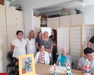 Seniorzy i pracownicy. Na blacie wystawa inspirowana wzorami kaszubskimi. Obrazki i papierowe laleczki.