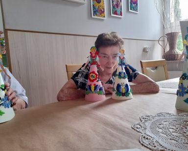 Uśmiechnięta seniorka siedzi przy stole. Przed nią papierowe laleczki wyklejane kolorowymi kulkami z bibuły.
