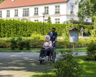 Wolontariuszka i seniorka podczas spaceru po Parku Oliwskim. W tle jasny budynek.