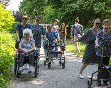 Seniorzy, wolontariusze i pracownicy na spacerze po Parku Oliwskim. Wokół zielone i kwitnące rośliny.