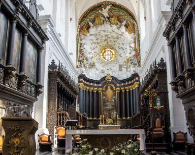 Wnętrze kościoła. Na wprost ołtarz z dekoracją z białych kwiatów.