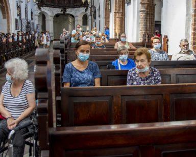 Wnętrze kościoła. Seniorzy, wolontariusze i pracownicy siedzą w drewnianych ławkach. Za nimi inni zwiedzający.