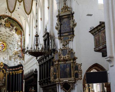 Wnętrze kościoła. Białe ściany, ozdobne żyrandole, obrazy w rzeźbionych ramach.