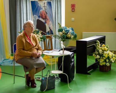Pani Otylia odmawia różaniec. W tle portret papieża Jana Pawła II i dekoracje z kwiatów.