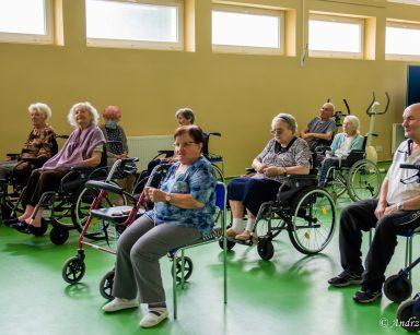 Jasna sala. Seniorzy siedzą i odmawiają różaniec.