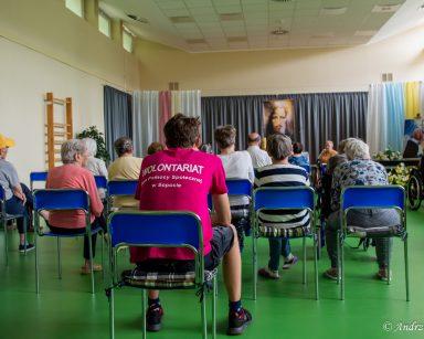 Na ścianie portret Jezusa. Na wprost niego siedzą seniorzy i wolontariusz.