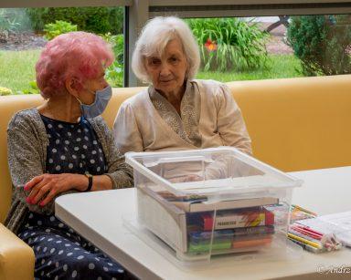 Przy stoliku rozmawiają dwie seniorki. Przed nimi na blacie pudełko z grami, kolorowe pisaki, arkusze papieru.